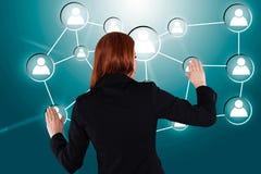 Mulher de negócios que toca em ícones humanos conectados Fotos de Stock Royalty Free
