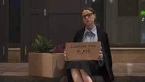 Mulher de negócios que toma procurando um sinal do cartão do trabalho da caixa na rua filme
