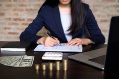 Mulher de negócios que trabalha com documento da declaração de rendimentos na tabela de madeira Conceito do negócio fotografia de stock royalty free