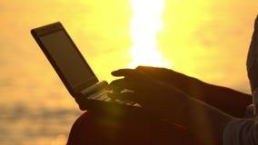 Mulher de negócios que trabalha com o portátil na praia Os remendos solares da luz de uma diminuição são refletidos em ondas do m video estoque