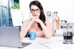 Mulher de negócios que trabalha com o portátil no escritório com filha atrás Imagem de Stock