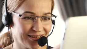 Mulher de negócios que trabalha em um centro de chamadas proffessional do serviço ao cliente que fala em auriculares 4K filme