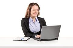 Mulher de negócios que trabalha em um portátil assentado em uma tabela Imagens de Stock