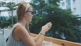 Mulher de negócios que trabalha no smartphone no café Mulher com cara séria usando o app no telefone celular vídeos de arquivo