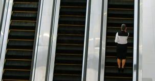 Mulher de negócios que usa a escada rolante ao falar no telefone celular 4k vídeos de arquivo