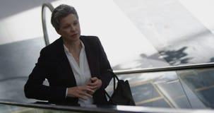 Mulher de negócios que usa a escada rolante em um escritório moderno 4k vídeos de arquivo
