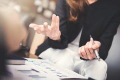 Mulher de negócios que usa o gesto de mão ao sentar-se e ao falar foto de stock