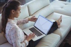 Mulher de negócios que usa o portátil ao descansar no sofá fotos de stock royalty free