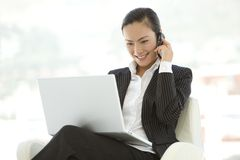 Mulher de negócios que usa o portátil em joelhos Foto de Stock