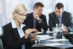 Mulher de negócios que usa o smartphone no escritório fotos de stock