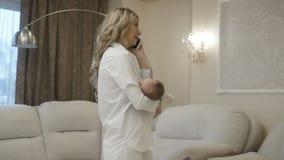 Mulher de negócios que usa o telefone celular ao babysitting video estoque