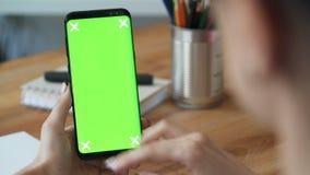 A mulher de negócios que usa o telefone celular com greenscreen no escritório vídeos de arquivo