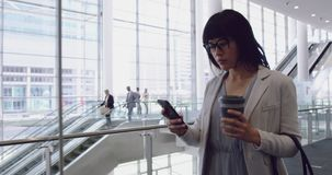 Mulher de negócios que usa o telefone celular e andando na entrada no escritório 4k filme