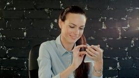 Mulher de negócios que usa o telefone celular, escrevendo o texto video estoque