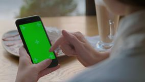 Mulher de negócios que usa o telefone celular móvel com o tela táctil verde no café Tela verde video estoque