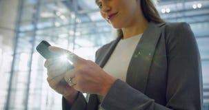 Mulher de negócios que usa o telefone celular na entrada no escritório 4k vídeos de arquivo