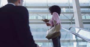 Mulher de negócios que usa o telefone celular na escada rolante em um escritório moderno 4k video estoque