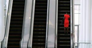Mulher de negócios que usa o telefone celular na escada rolante 4k filme
