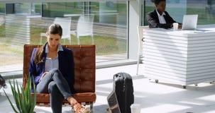 Mulher de negócios que usa o telefone celular no sofá 4k filme