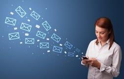 Mulher de negócios que usa o telefone com conceito do correio ao redor foto de stock