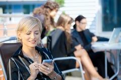 Mulher de negócios que usa o telefone esperto Imagens de Stock