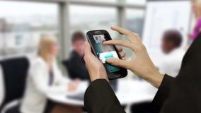 Mulher de negócios que usa o telefone esperto na reunião filme