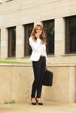 Mulher de negócios que usa o telemóvel ao andar na rua fotografia de stock royalty free