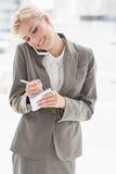 Mulher de negócios que usa seu smartphone e escrevendo notas Fotografia de Stock