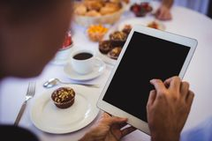 Mulher de negócios que usa a tabuleta digital no restaurante fotografia de stock