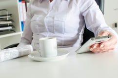 Mulher de negócios que usa um smartphone durante a ruptura de café Fotos de Stock