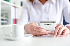 Mulher de negócios que usa um smartphone durante a ruptura de café Imagem de Stock