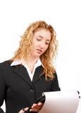 Mulher de negócios que verific seu bloco de notas sobre imagens de stock