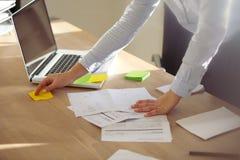 Mulher de negócios que verifica notas no post-it Imagens de Stock