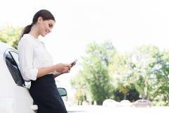 Mulher de negócios que verifica o smartphone, inclinando-se no carro fora fotografia de stock royalty free