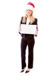Mulher de negócios que veste o chapéu de Santa e que guarda um cartaz vazio Fotos de Stock Royalty Free