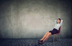 Mulher de negócios de refrigeração que senta-se na cadeira imagem de stock