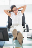 Mulher de negócios relaxado que senta-se em sua mesa com seus pés que olham acima a câmera Fotografia de Stock