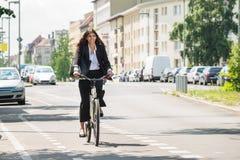 Mulher de negócios Riding Bicycle imagens de stock royalty free