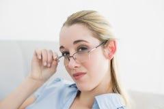 Mulher de negócios séria calma que senta-se em vidros vestindo do sofá Imagem de Stock Royalty Free