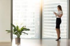 Mulher de negócios séria nova que guarda a tabuleta que está o completo-le próximo Fotografia de Stock