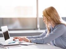 Mulher de negócios séria que datilografa no portátil no escritório fotos de stock