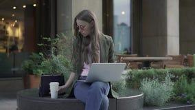 Mulher de negócios séria que trabalha com o portátil no café do verão e no café bebendo filme