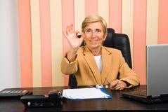Mulher de negócios sênior feliz que mostra a mão aprovada do sinal fotografia de stock royalty free