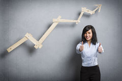 Mulher de negócios satisfeito que guarda os polegares acima na frente da carta de ascensão Imagem de Stock