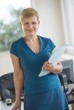 Mulher de negócios segura Holding File While que está na mesa Fotografia de Stock Royalty Free