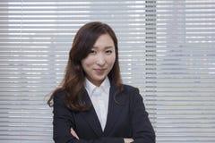 Mulher de negócios segura que está com seus braços cruzados Imagens de Stock Royalty Free
