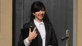 Mulher de negócios de sorriso atrativa que usa uma tabuleta digital ao estar na frente da porta do escritório filme