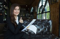 A mulher de negócios de sorriso feliz com polegares levanta o gesto que olha a câmera que senta-se em um sofá Imagem de Stock Royalty Free