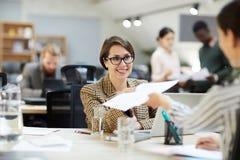 Mulher de negócios de sorriso Giving Documents ao colega fotos de stock