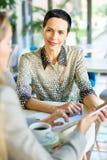 Mulher de negócios de sorriso Meeting Partners no café imagem de stock